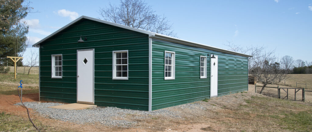 Green metal structure with white doors and trim. New Freckled Farm Soap Company soap facility.